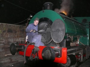Picture of a man shovelling ash out of the smokebox of a steam engine