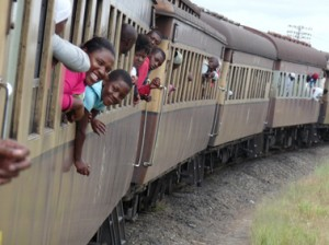 Picture of passengers hanging out of the window of an elderly African passenger train